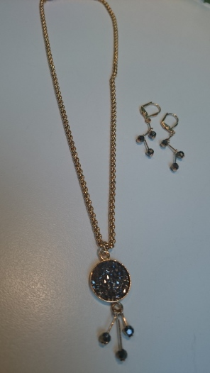 Setje bestaande uit oorbellen en ketting 'klein', met goudkleurige basis en goud-grijze Swarovski steentjes €50,00 per setje