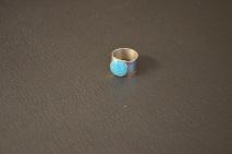 Zilverkleurige ring met lichtblauwe dots overgoten met hars €15,00