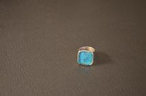 Zilverkleurige ring met vierkant en blauwe Swarovski overgoten met hars €15,00